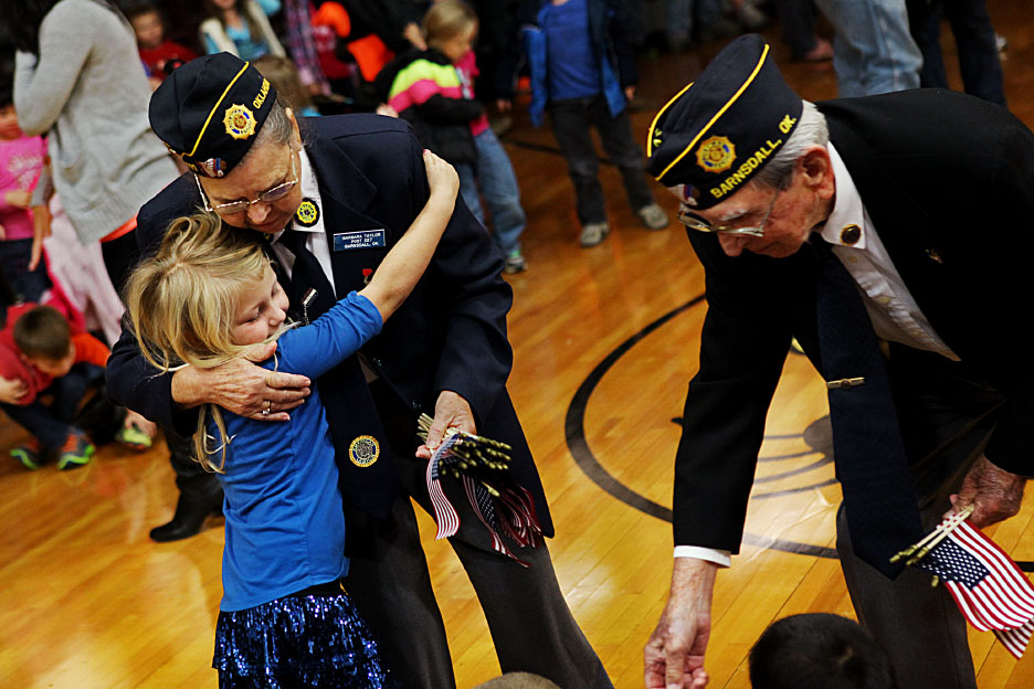 First grader Melody Hanes hugs veteran Barbara Taylor as she hands out small flags to students after the assembly Monday morning. Taylor introduced herself to the crowd as an army cook from Barnsdall.