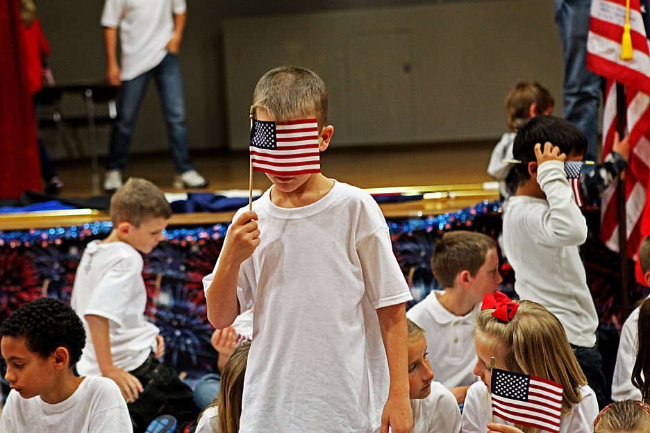 Second grade students goof off with their American flags before heading back to class after the Veterans Day assembly.