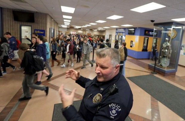 Bremerton school resource officer Matt Strombach, of the Bremerton Police Department, talks about his role at the school as students head for their classes after lunch period Tuesday at Bremerton High School. (Meegan Reid / Kitsap Sun)