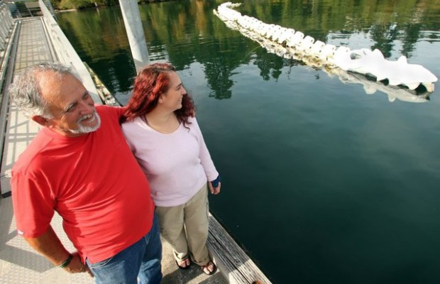 Terry Asla and daughter Colleen Asla-Dobbin admire their sculpture from the dock at the Brownsville Marina. (Meegan Reid / Kitsap Sun)